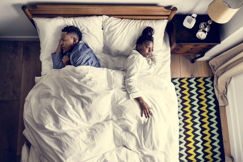 African American couple sleeping back to back stock photography