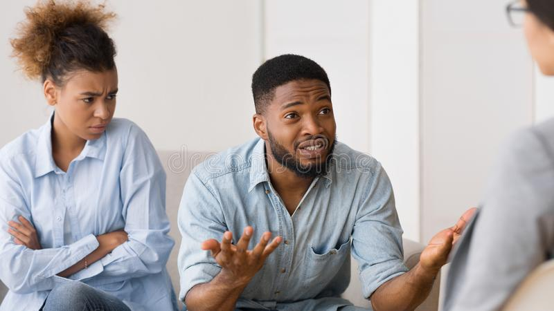 African American Couple Talking To Psychologist During Therapy Session. Afro Husband Sharing Family Problems Sitting Next To Dissatisfied Wife At Counselor`s stock photos