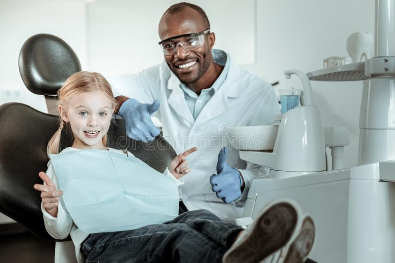 African American dentist in full uniform sitting behind his little patient royalty free stock images