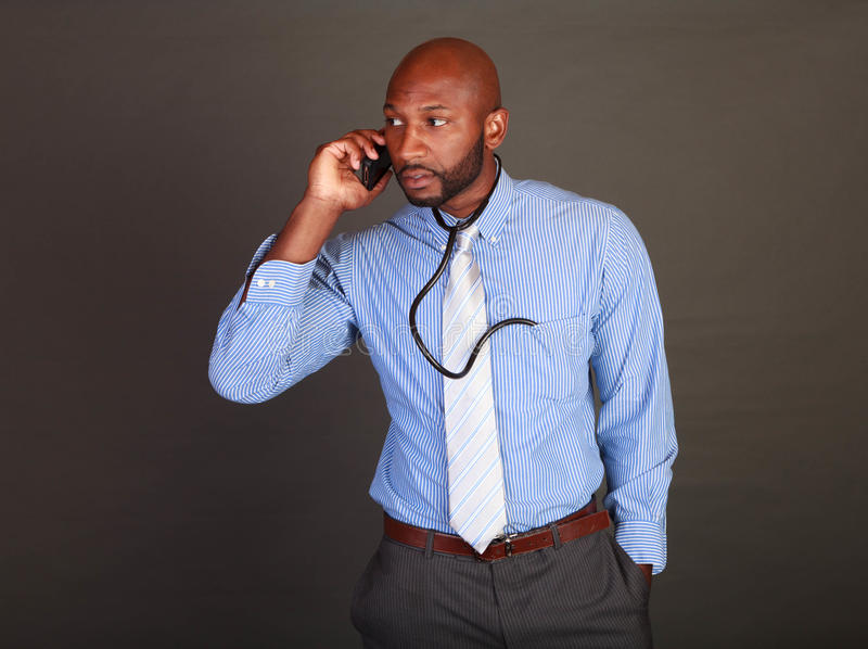 Download African American Doctor Checks His Phone Stock Photo - Image: 28054500