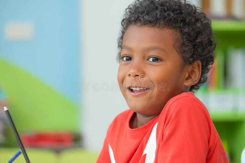 African American ethnicity kid holding group of color pencil smiling at library in kindergarten preschool classroom.education con stock photos