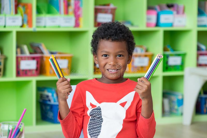 African American ethnicity kid holding group of color pencil smiling at library in kindergarten preschool classroom.education con stock image