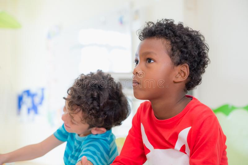 African American ethnicity kid with moody emotion sitting in classroom in kindergarten ,education concept stock photo