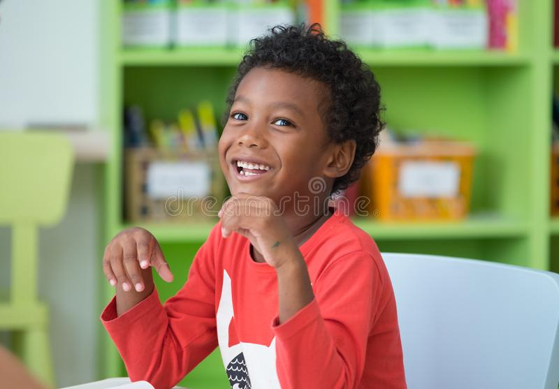 African American ethnicity kid smiling at library in kindergarten preschool classroom.happy emotion.education concept. stock photos
