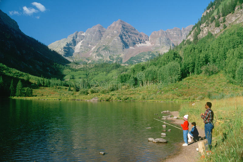 African american family. African American man and two children fishing on Maroon Lake, Colorado stock photos