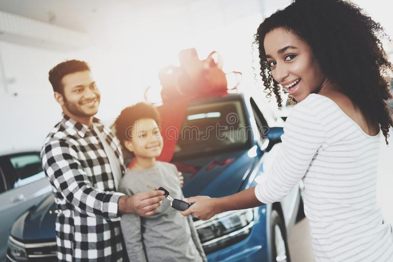 African american family at car dealership. Father, mother and son near new car. Man is giving keys to woman. African american family at car dealership. Father royalty free stock photography