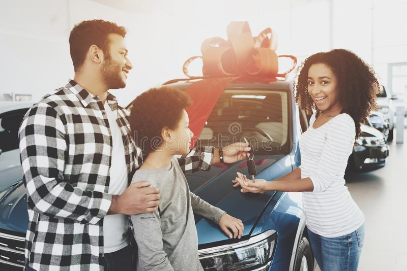 African american family at car dealership. Father, mother and son near new car. Man is giving keys to woman. African american family at car dealership. Father stock images