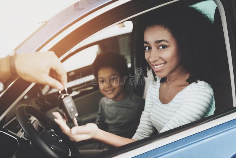 African american family at car dealership. Father, mother and son near new car. Man is presenting keys to woman. African american family at car dealership stock photo
