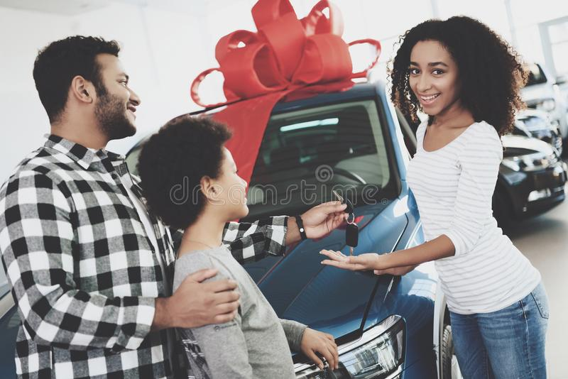 African american family at car dealership. Father, mother and son near new car. Man is presenting keys to woman. African american family at car dealership stock photography