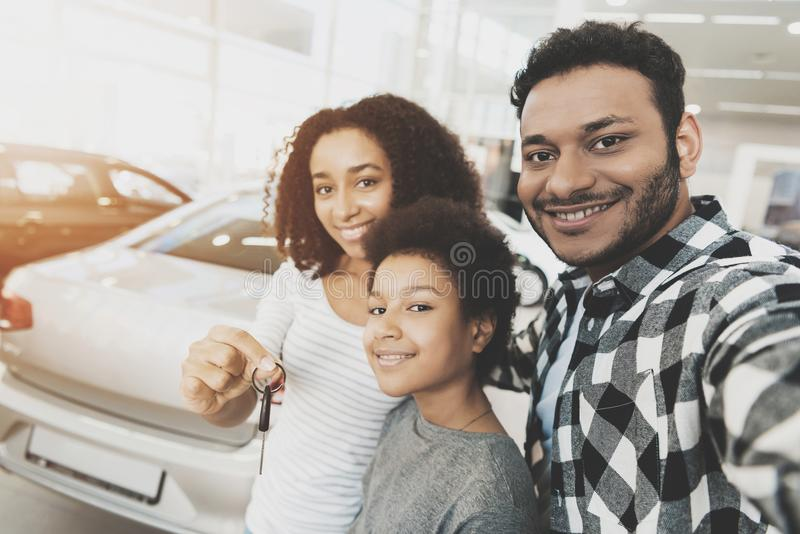 African american family at car dealership. Mother, father and son are taking selfie with keys for new car. African american family at car dealership. Mother stock photography