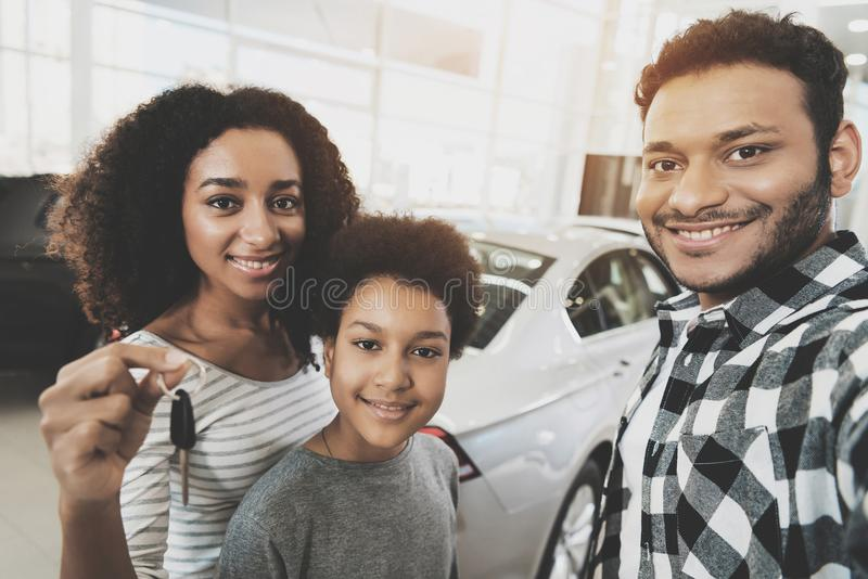 African american family at car dealership. Mother, father and son are taking selfie with keys for new car. African american family at car dealership. Mother royalty free stock images