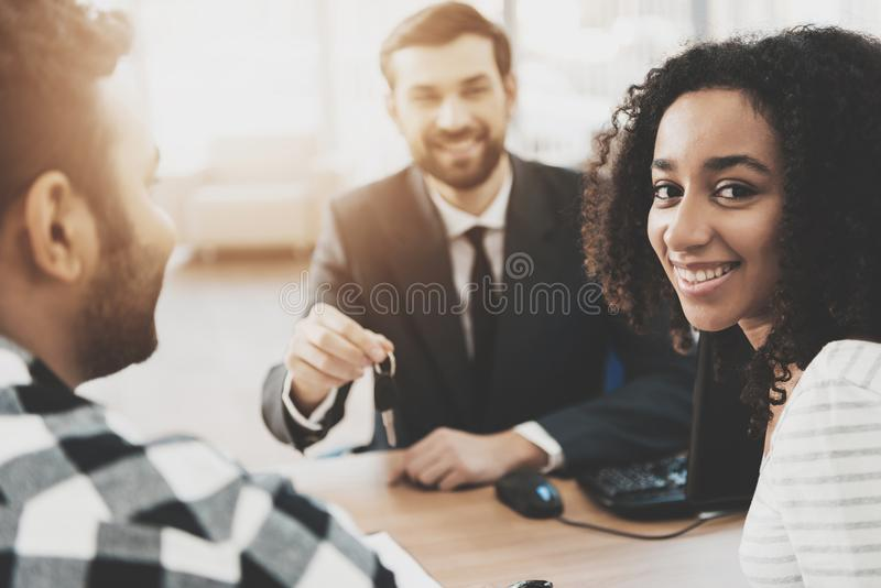 African american family at car dealership. Salesman is presenting keys for new car. royalty free stock photo