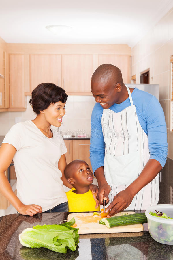 African american family cooking. Happy african american family of three cooking in home kitchen royalty free stock images