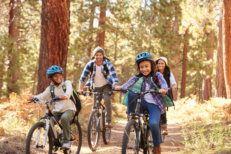 African American Family Cycling Through Fall Woodland royalty free stock image