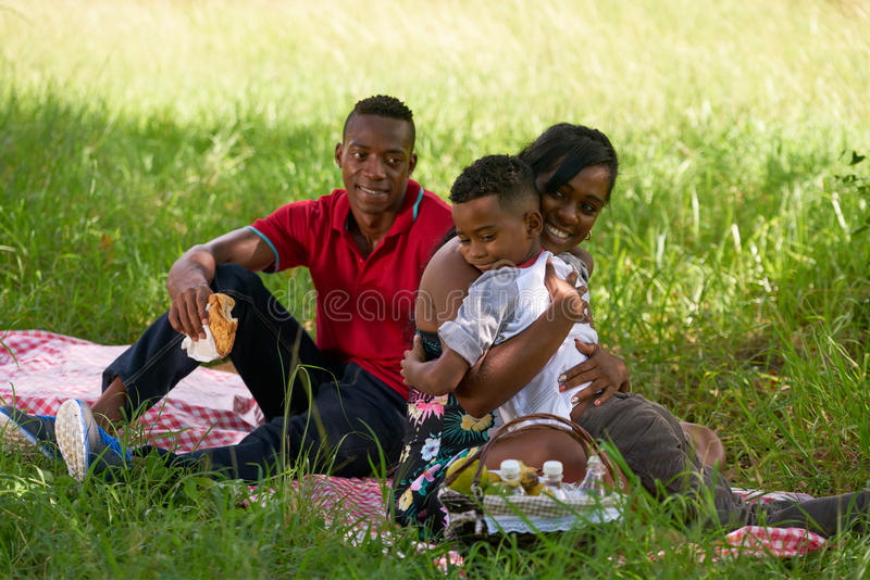 African American Family With Father Mother Child Hugging In Park stock photo