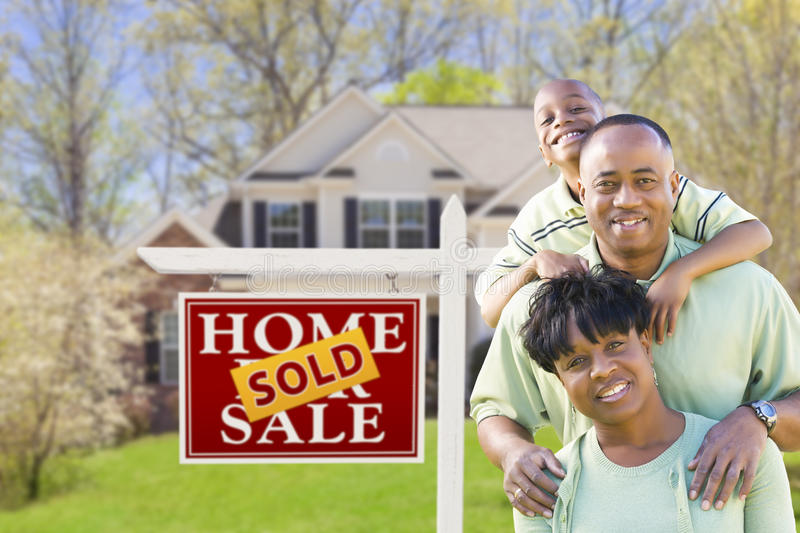 African American Family In Front of Sold Sign and House. Happy African American Family In Front of Sold Real Estate Sign and House royalty free stock images
