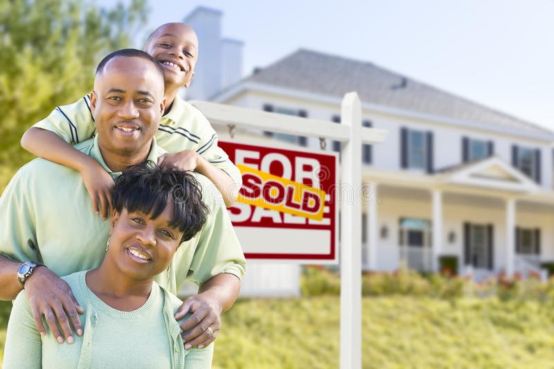 African American Family In Front of Sold Sign and House. Happy African American Family In Front of Sold For Sale Real Estate Sign and House royalty free stock photography