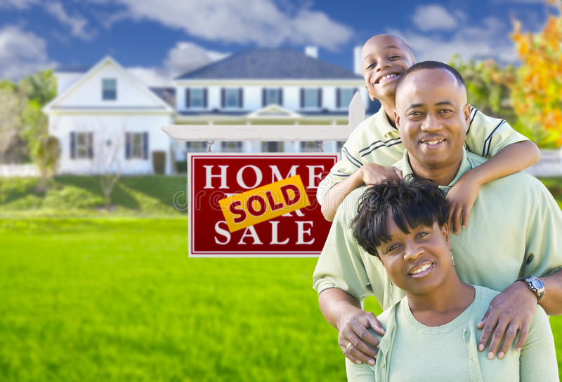 African American Family In Front of Sold Sign and House. Happy African American Family In Front of Sold For Sale Real Estate Sign and House royalty free stock image