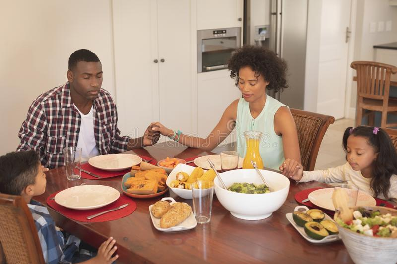 African American family with holding hands and eyes closed praying together at dining table stock images