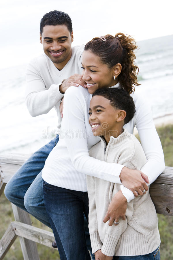 African-American family hugging at beach stock photo