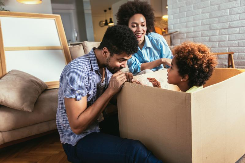 African American family, parents and daughter, unpacking boxes and moving into a new home stock photo