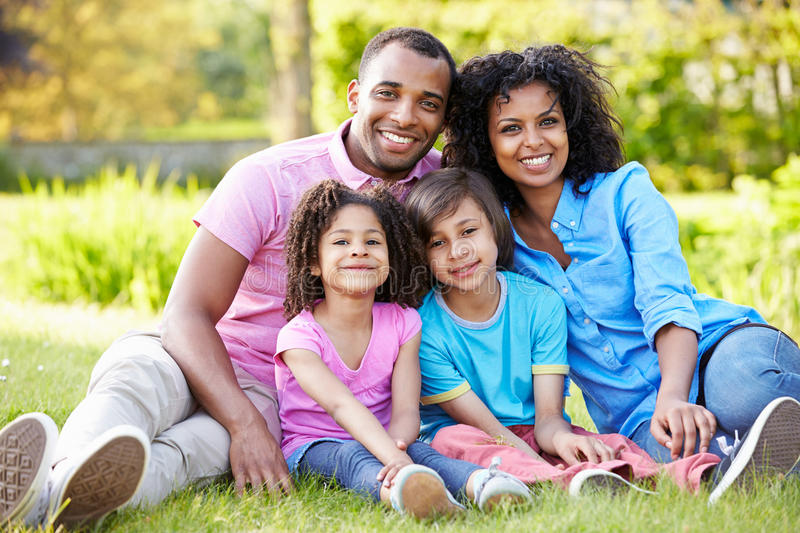 African American Family Sitting In Garden stock photos