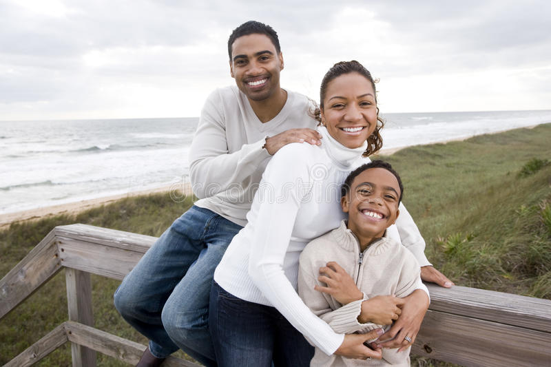 African-American family smiling, hugging at beach stock images