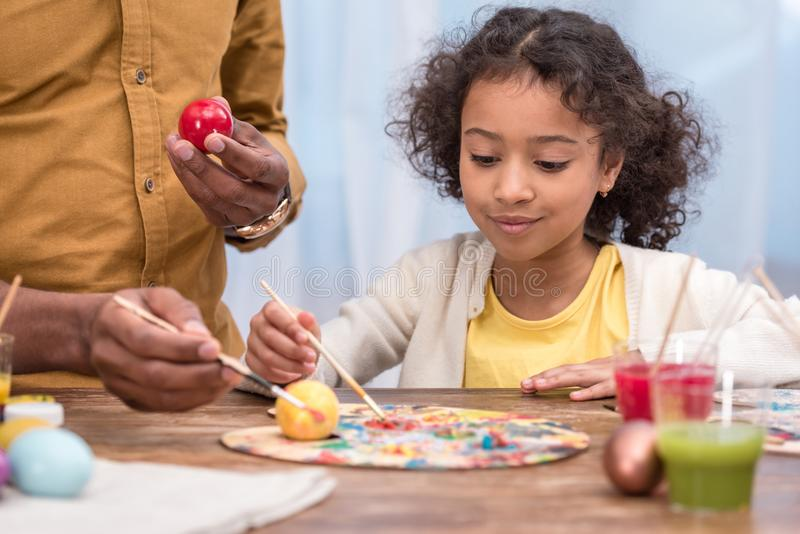 African american father and adorable daughter painting easter eggs with poster paints. Cropped image of african american father and adorable daughter painting royalty free stock photo
