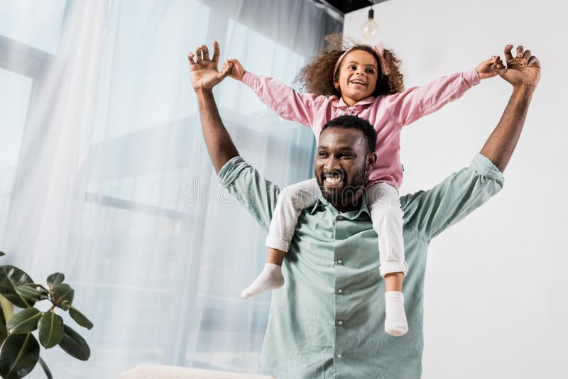 african american father carrying daughter on neck and playing in stock image