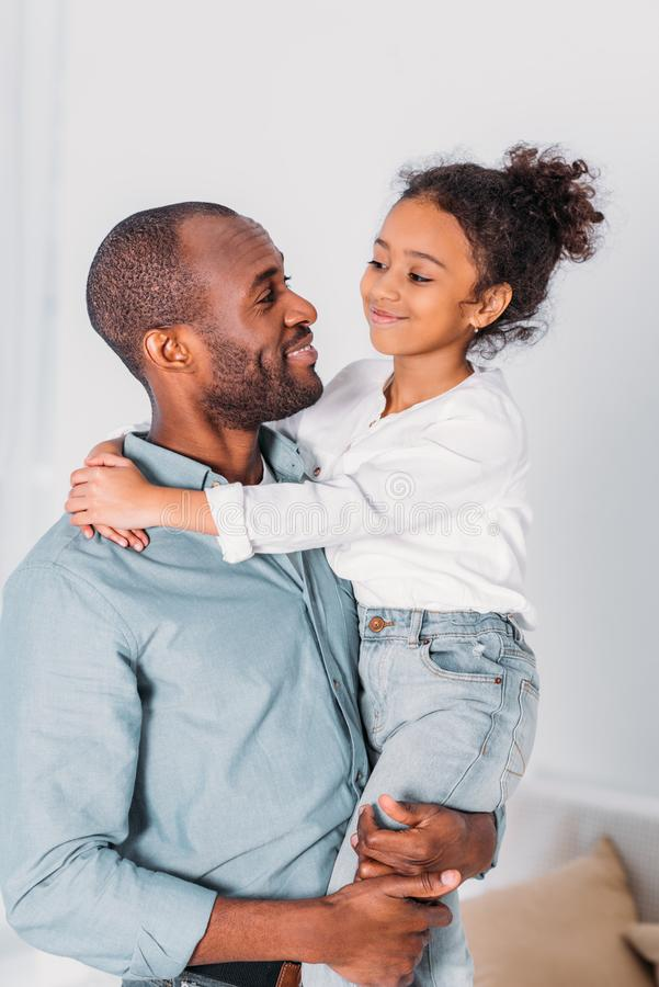 african american father carrying and hugging daughter stock photography
