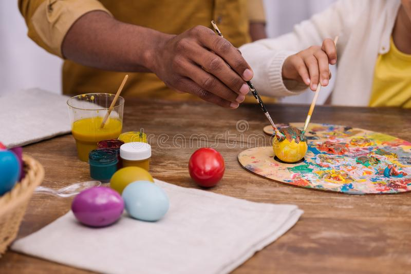 African american father and daughter painting easter eggs with poster paints. Cropped image of african american father and daughter painting easter eggs with stock images