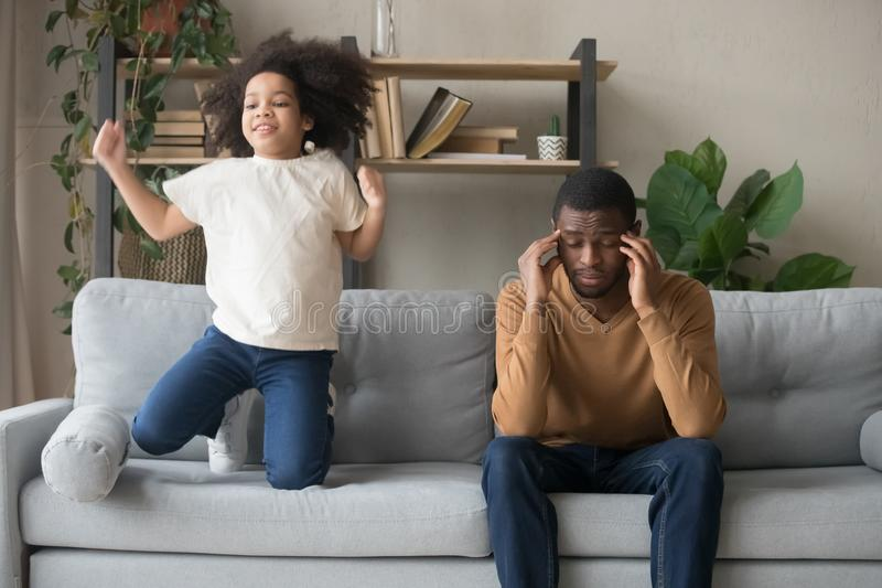 African American father having problem with noisy naughty daughter. African American father having problem with noisy naughty preschool daughter jumping on couch royalty free stock photo