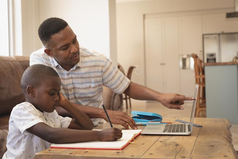 African American father helping his son with homework on laptop at table royalty free stock images