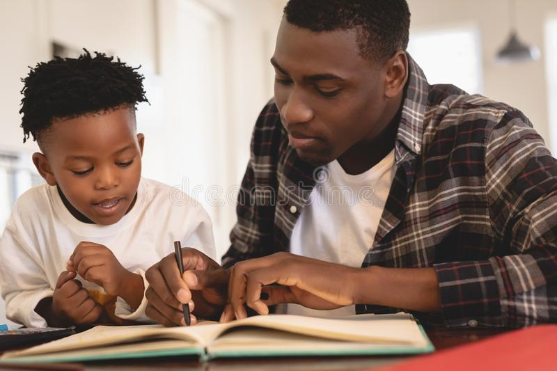 African American father helping his son with homework at table. Front view of African American father helping his son with homework at table royalty free stock photo