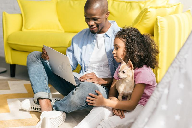 African american father and little daughter with dog using laptop together. At home royalty free stock photography
