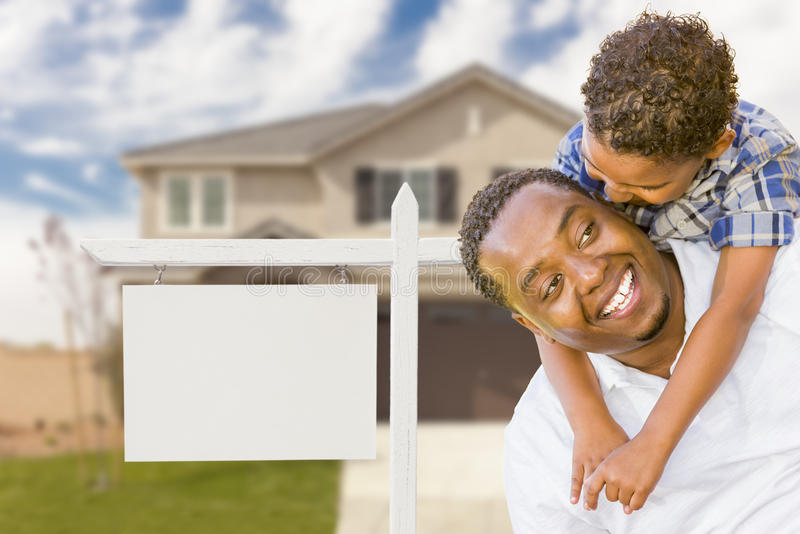 African American Father and Mixed Race Son In Front of Blank Real Estate Sign and House stock photography