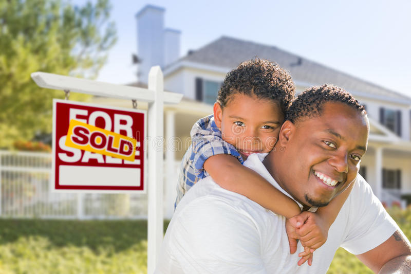 African American Father and Mixed Race Son, Sold Sign, House. African American Father and Mixed Race Son In Front of Sold Home For Sale Real Estate Sign and New stock photos