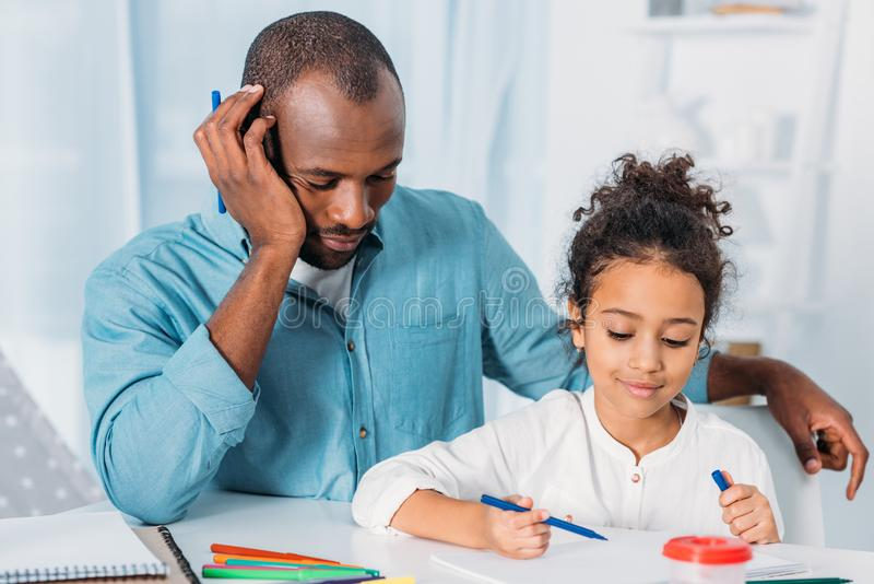 african american father napping and daughter drawing royalty free stock photography