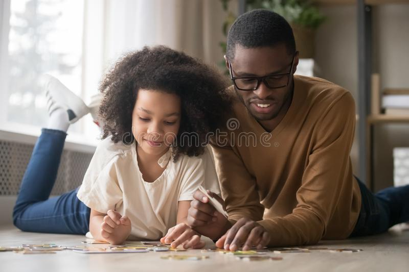 African American father with preschool daughter assembling puzzle. Happy African American father in glasses with preschool daughter assembling jigsaw puzzle stock image