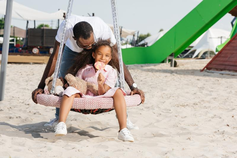 african american father pushing happy daughter with lollipop on spider web nest swing royalty free stock photos