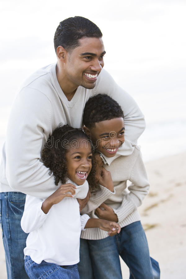 African-American father and two children on beach stock photo
