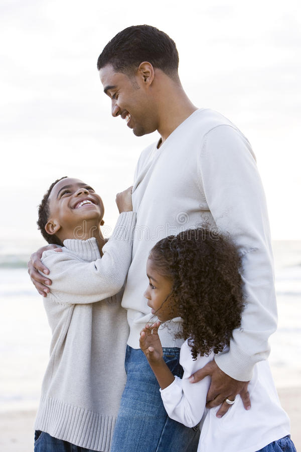 African-American father and two children on beach stock image