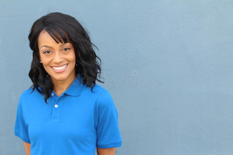 African American female blue collar worker posing in uniform crossing isolated on blue stock photography