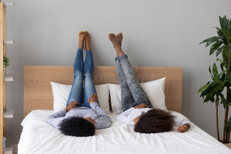 Black mother and daughter relax on bed talking. African American female friends lying on their backs on bed talking, happy black mom or nanny and teen daughter stock photography