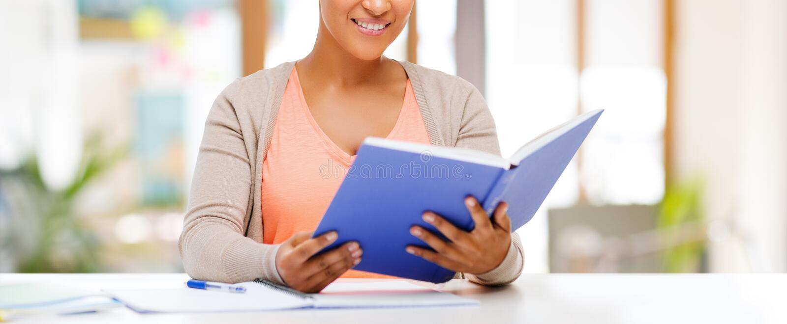 African american female student reading book stock images