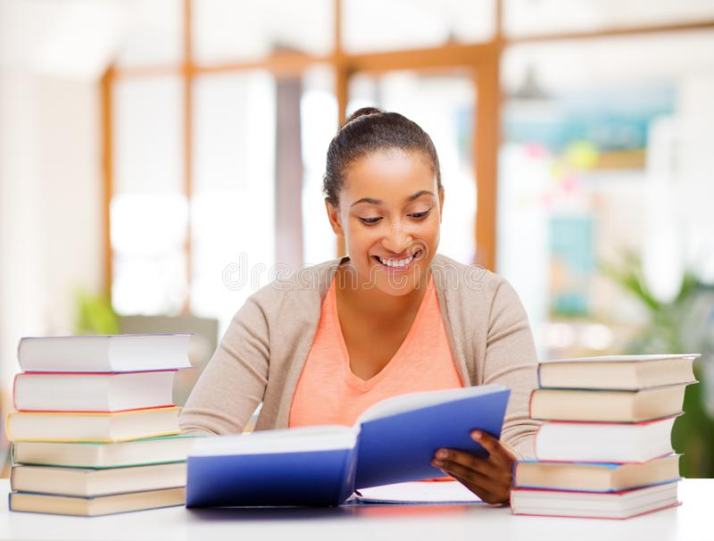 African american female student reading book stock photo