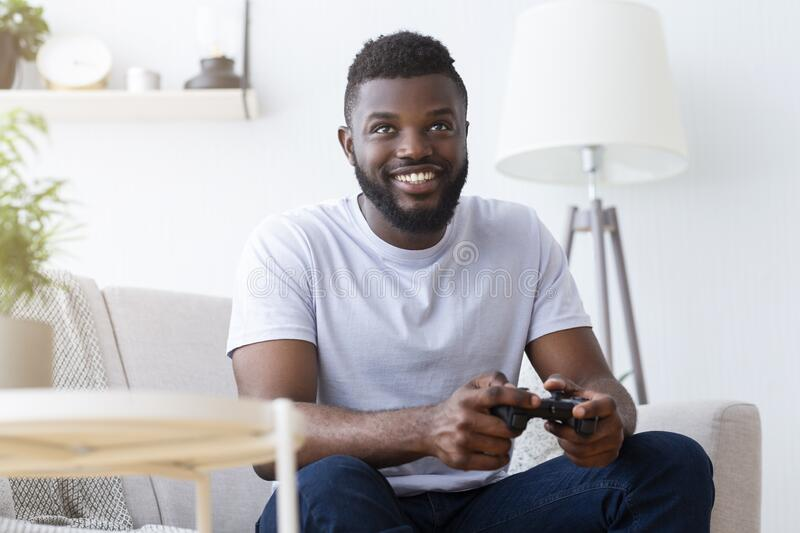 African american gamer playing on gamepad at home royalty free stock photos