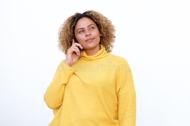 African american girl with curly hair talking on mobile and thinking phone by white background royalty free stock photography