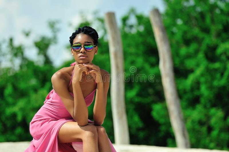 African American girl with dreadlocks, wearing sunglasses, pink dress, sits and dreams on top of a hill on a Sunny day. Portrait. Close-up. Horizontal view royalty free stock photography