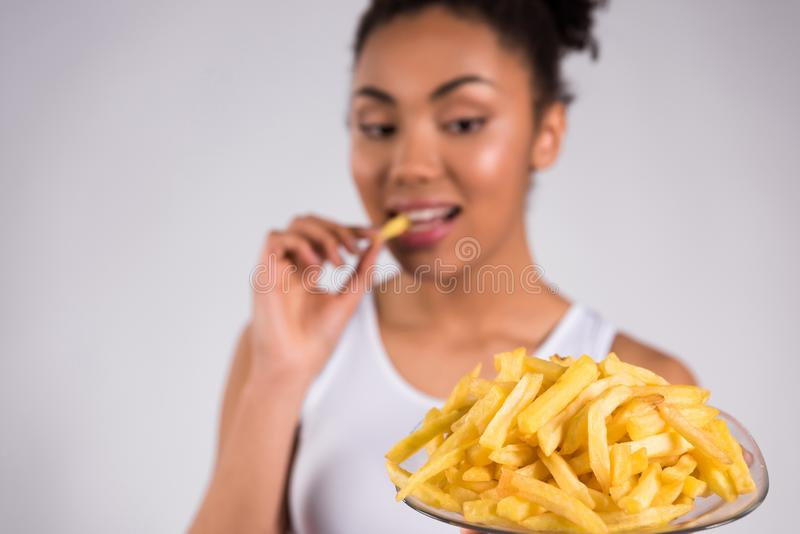 African American girl eating fries . royalty free stock photos
